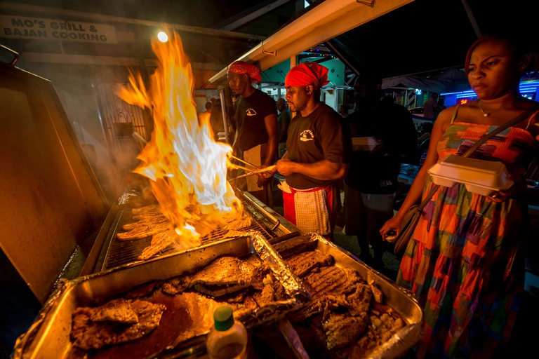 Cooks frying up fish on a BBQ at Oistins fish fry night, Oistins, parish of Christ Church, Barbados , Caribbean, West Indies