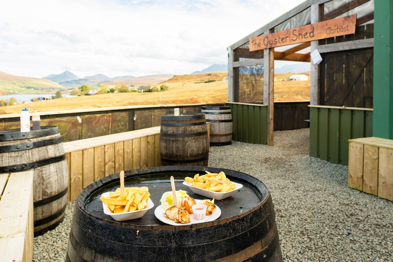 The Oyster Shed with fresh scallops and chips on whisky barrel tables,  Carbost, Highland, Isle of Skye, Scotland, UK