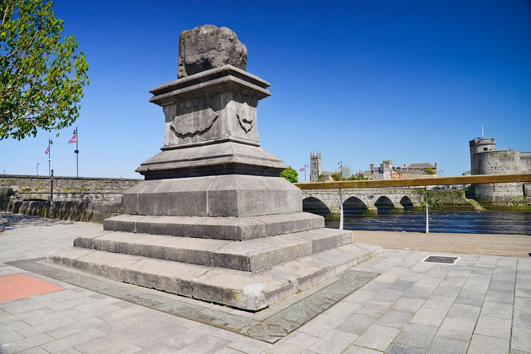 Ireland, County Limerick, Limerick City, The Treaty Stone with the River Shannon and St John's Castle.