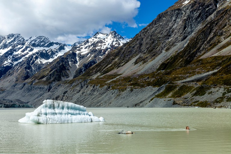 A Tourist Swimming In The Glacial Hooker Lake At The End Of The Hooker Valley Track, Aoraki/Mt Cook National Park, South Island, New Zealand