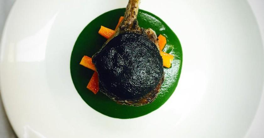 Lomo de Cordero con Trompetas de la Muerte y Zanahorias  Roasted Lamb Loin with Black Trumpets Mushrooms and Carrots | Image Courtesy of Ananda 141