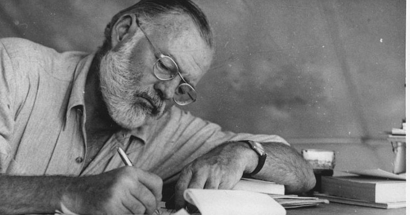 Ernest Hemingway writing at Campsite in Kenya | © Look Magazine/WikiCommons