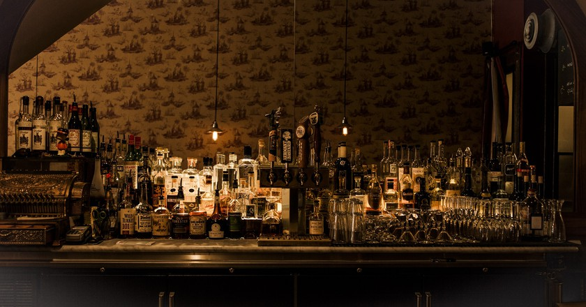 A vintage cash register anchors the well-stocked bar | Courtesy of Two Sisters Bar and Books
