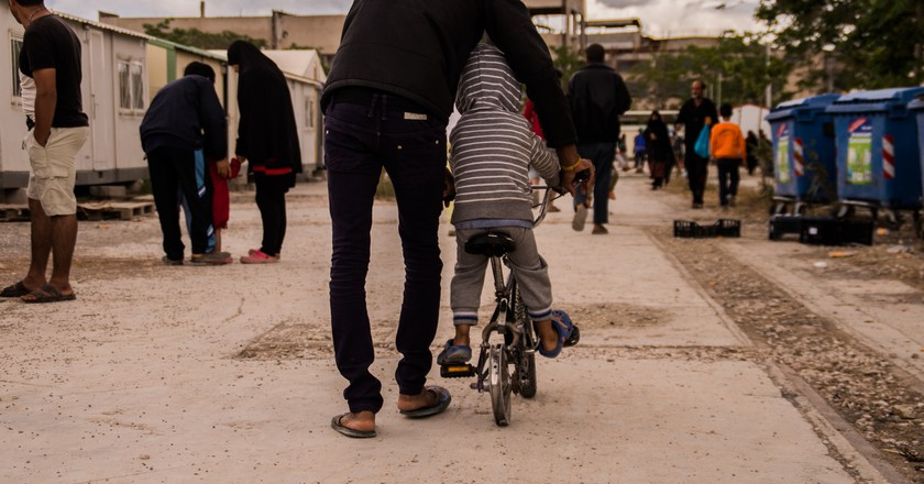 A father teaches his son how to cycle on a flat-tire bike in Eleonas Refugee Camp | © Camille Gazeau