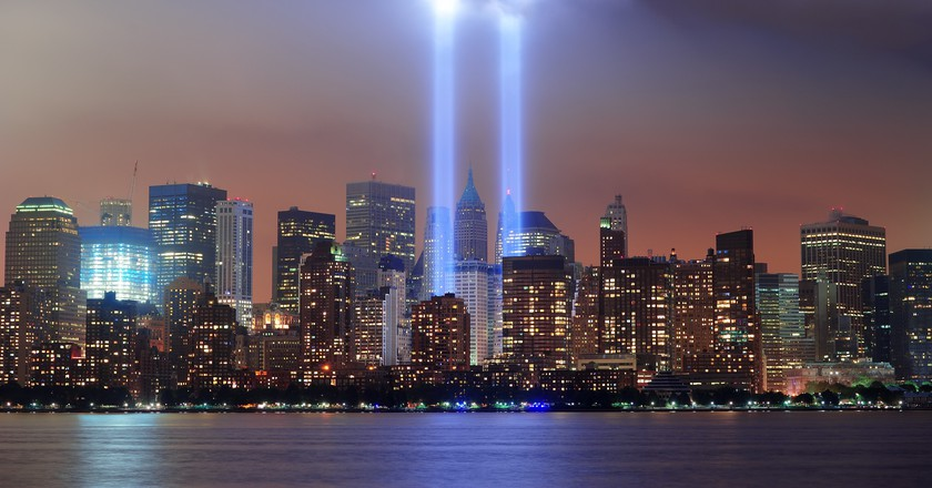 New York City Manhattan downtown skyline at night from Liberty Park with light beams in memory of September 11 viewed from New Jersey waterfront.| ©Songquan Deng / Shutterstock