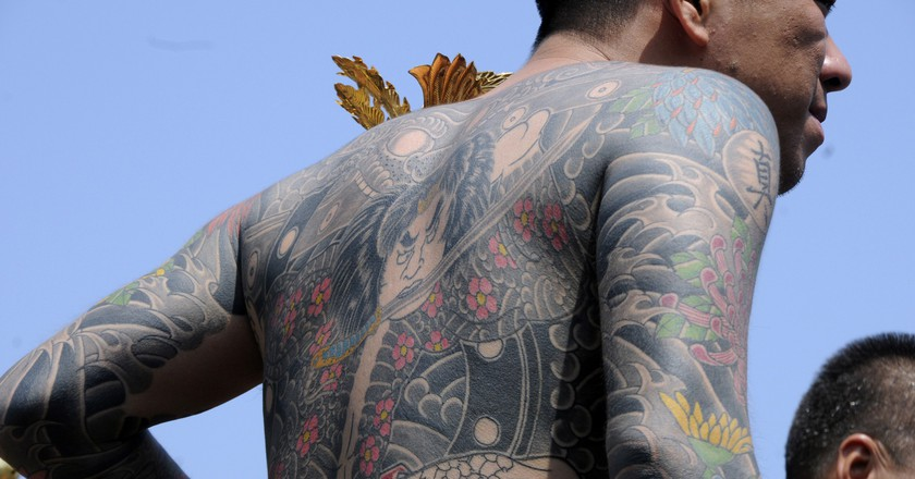 A man with yakuza-style tattoos at a festival |