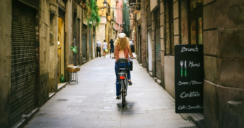 Woman riding bicycle through old street of Barcelona | © Alexandr23/Shutterstock