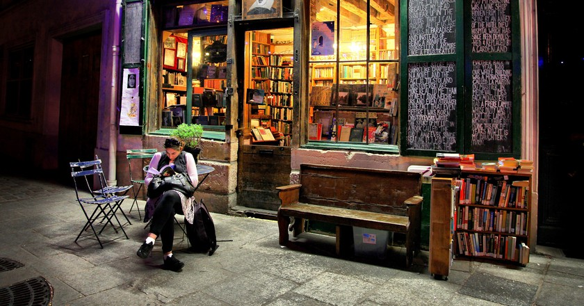 An engrossed reader outside Shakespeare and Company│© Catherine Zenino