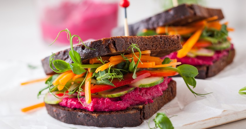 Gluten-free vegan sandwiches with beet hummus, raw vegetables and sprouts │ © sarsmis / Shutterstock