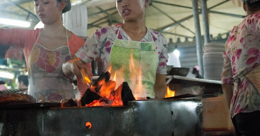Vietnamese cooks in a steaming hot street food marquee © Michael Davis-Burchat / Flickr