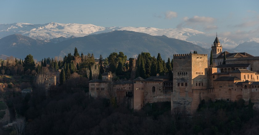 Alhambra Palace in Granada, Spain with Sierra Nevada mountains in snow at the background| © Igor Dymov/Shutterstock