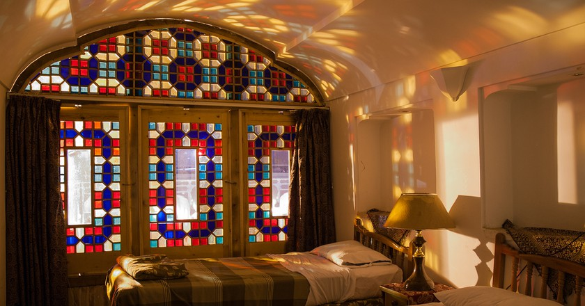 Sunlight streaming through stained glass windows lights this room in Yazd   © Julia Maudlin / Flickr