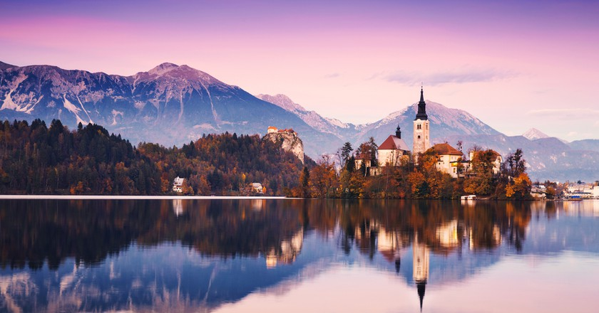 Amazing View On Bled Lake on Sunset. Autumn in Slovenia, Europe. View on Island with Catholic Church in Bled Lake with Castle and Mountains in Background | © Natalia Deriabina / Shutterstock