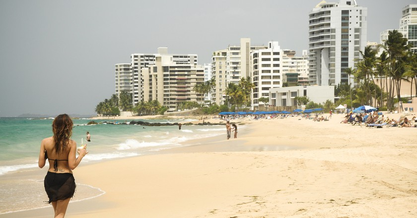 Woman walking on a beach in San Juan | © Andrew Hart/ Flickr