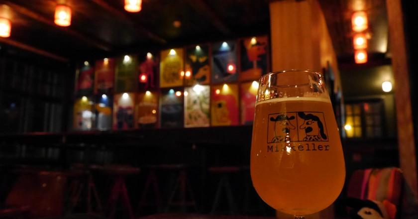 "<a href = ""https://www.flickr.com/photos/activesteve/30498779241/in/photolist-NqvGcq-Nt5dvp""> Enjoying a Beer at Mikkeller | © ActiveSteve/Flickr"