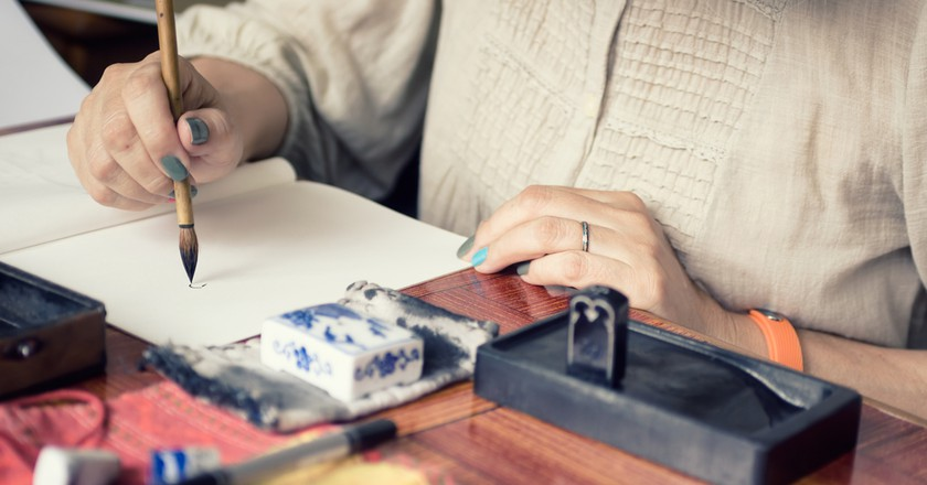 Woman with a calligraphy brush | Shutterstock