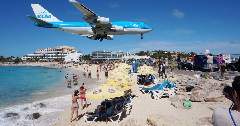Airplanes landing at the Princess Juliana Airport fly over beachgoers | © EQRoy/Shutterstock