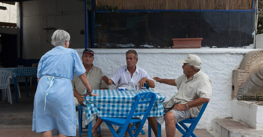 Santorini locals sitting down for lunch | © StockStudio/Shutterstock