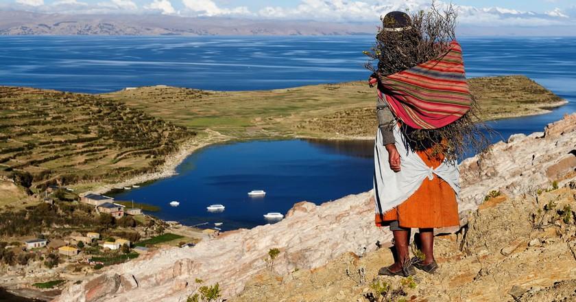 A native woman looks out over Lake Titicaca from Bolivia's Isla del Sol   © Rafal Cichawa / Shutterstock