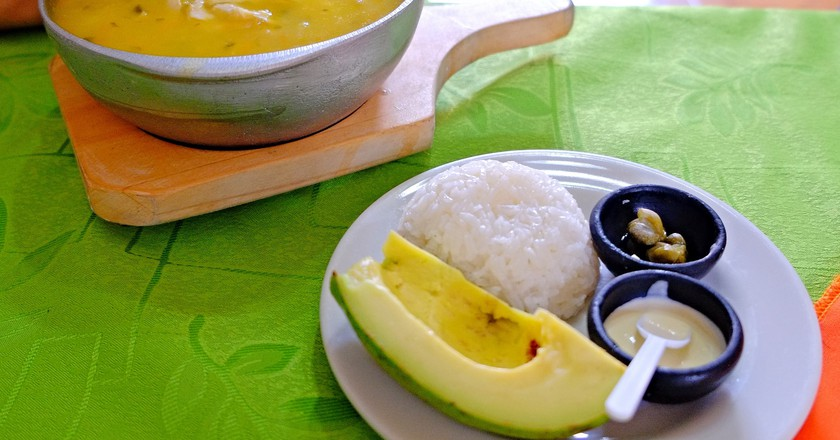"""<a href=""""https://www.flickr.com/photos/61266278@N00/25952438801"""" target=""""_blank"""" rel=""""noopener noreferrer"""">A full Colombian-style ajiaco with rice and avocado   © Reg Natarajan / Flickr</a>"""