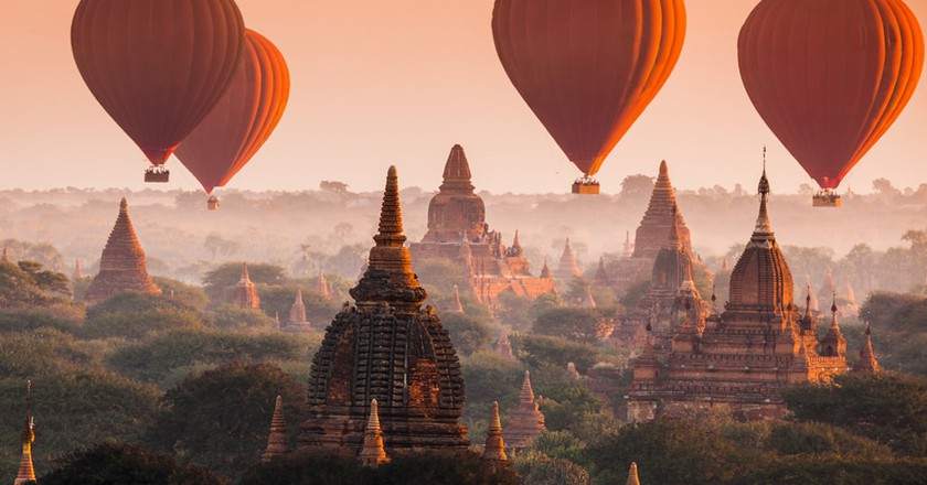 Hot air balloons rise over misty Bagan early in the morning   © Ikunl / Shutterstock