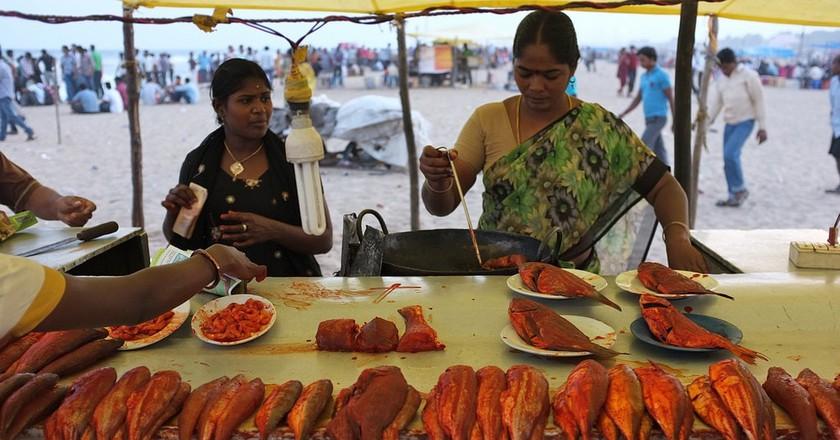 A vendor making fried fish at a stall in Chennai's Marina Beach