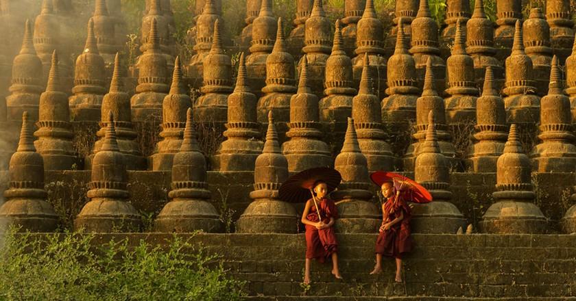 Novice monks hold traditional umbrellas at Ratanabon Paya in Mrauk U, Myanmar   © saravutpics / Shutterstock