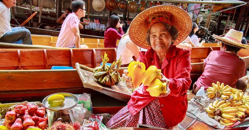 Thai fruit vendor at Damnoen Saduak floating market | © puwanai / Shutterstock