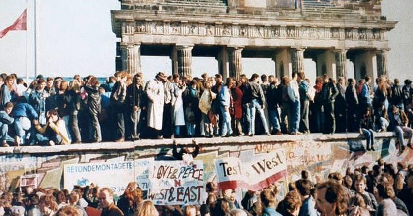 West and East Germans stand on a fallen Berlin Wall | © Lear 21 / WikiCommons