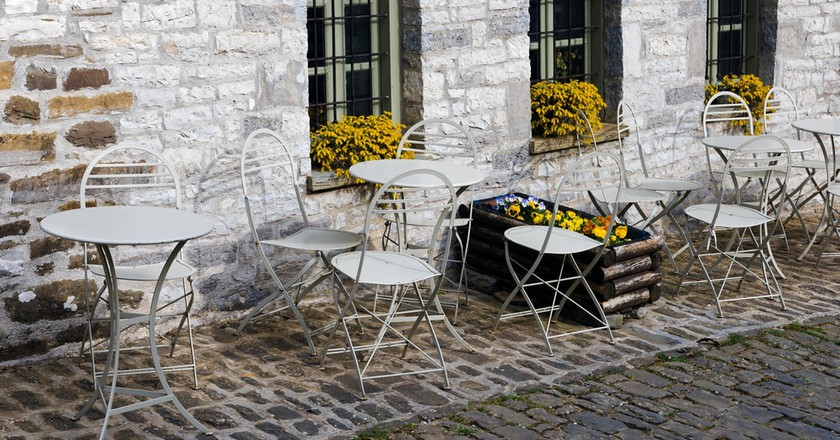 Tables in front of a traditional stone village of Papigo in Epirus, Greece   ©  dinosmichail / Shutterstock