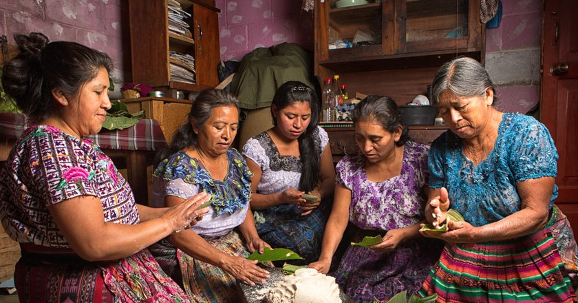 Tzutujil mayan women preparing traditional food together, Guatemala | © Barna Tanko/Shutterstock