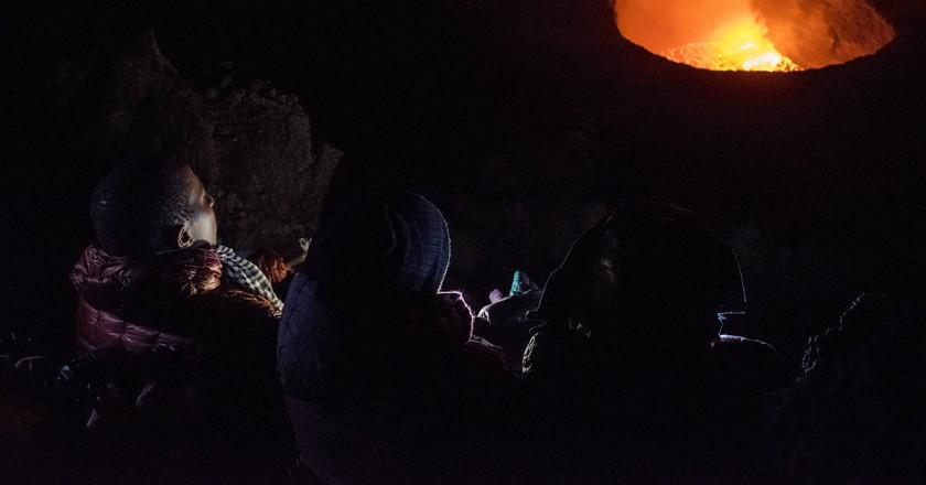 Ugandan adventurers watching the active volcano atop Mount Nyirangogo in Democratic Republic of Congo