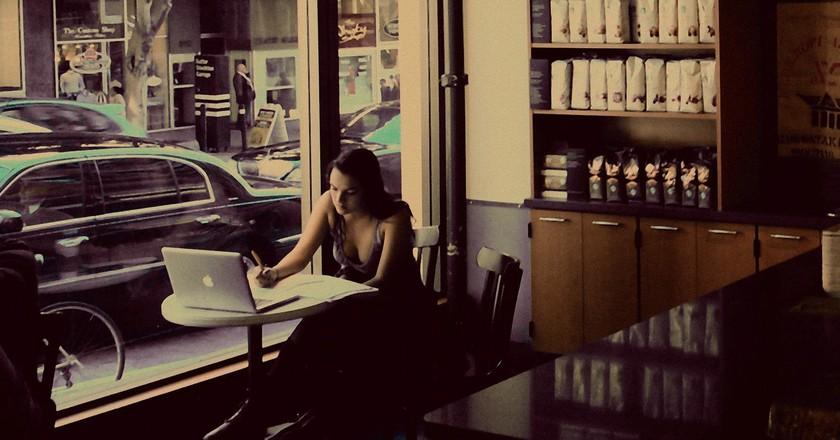 Girl writing in coffee shop.