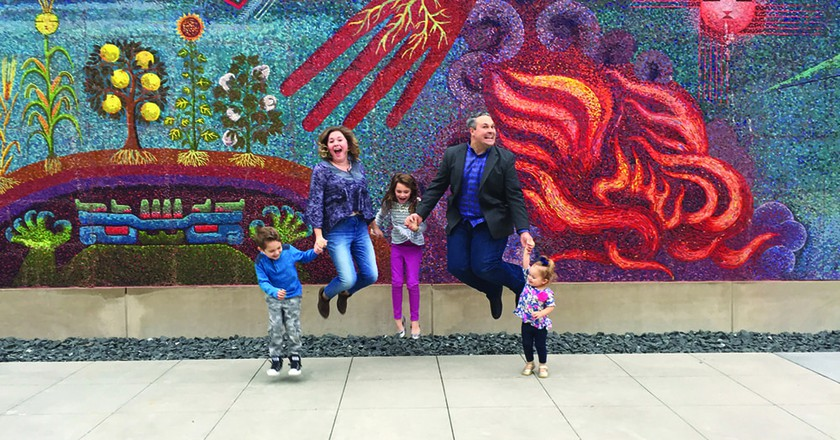 A family jumps for joy in front of Miguel Covarrubias' 'Genesis, The Gift of Life,' 1954 at the DMA