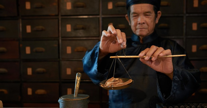 Traditional practitioner weighting lucidum for the recipe | © Dragon Images/Shutterstock