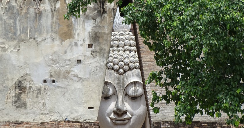 A peaceful Buddha face peering through a wall, Sukhothai | © Adam Jones / Flickr