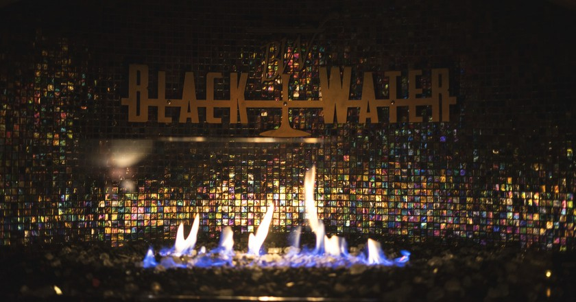 Drink a cocktail by Black Water's cozy fireplace.