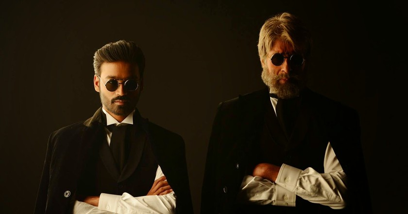 Actor Dhanush (Left) alongside veteran actor Amitabh Bachchan in a still from his last Bollywood release Shamitabh
