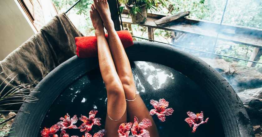 Woman relaxing in round outdoor bath with tropical flowers