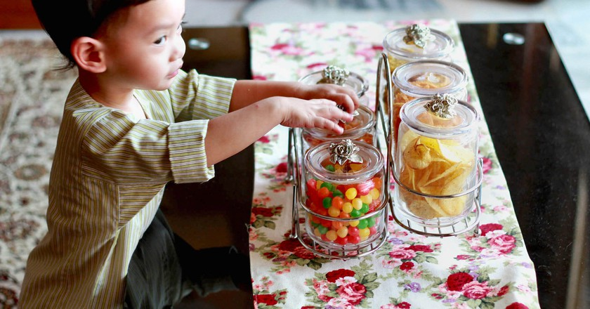 Young child taking Hari Raya snacks from jar