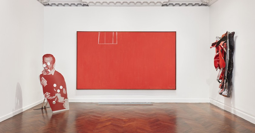 Installation view of 'Reds,' featuring Cady Noland's 'Bluewald' (1989) on the left, Robert Motherwell's 'Open No. 153: In Scarlet with White Line' (1970) in the center, and John Chamberlain's 'Funn' (1978) on the right