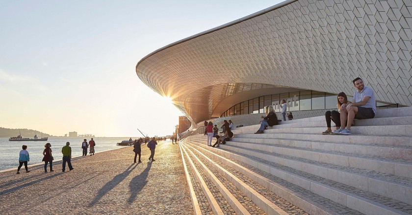 Waterfront steps and curvaceous facade with visitors. MAAT, Lisbon, Portugal