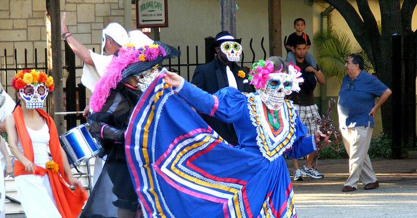 A woman dances during the La Villita parade dressed as a calavera catrina