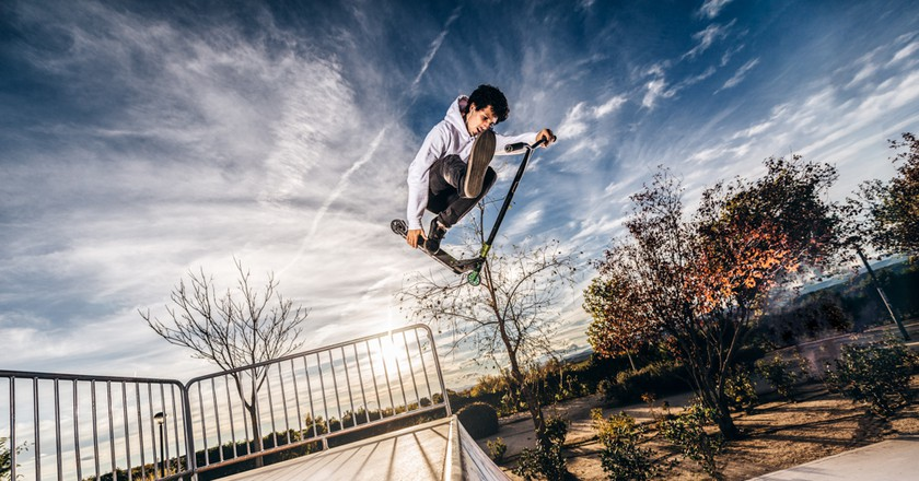 A young man with a scooter makes a jump at a skatepark