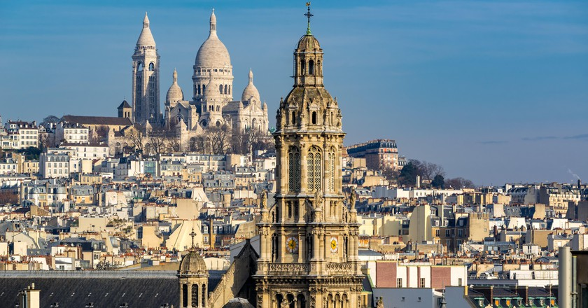 Blue skies enhance the scene of rooftops and the Sacré-Coeur Basilica in Montmartre, Paris.
