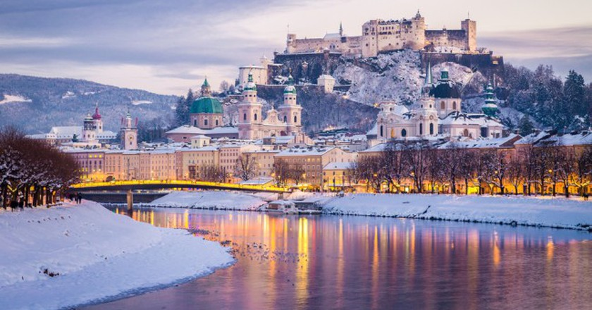Salzburg with famous Festung Hohensalzburg and Salzach river illuminated in beautiful twilight during scenic Christmas time | © Canadastock/Shutterstock