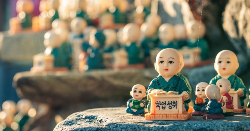 figurines scattered around the rocks of Haedong Yonggungsa Temple in Busan, South Korea. The figurines are meant to encourage academic achievement   © Vincent St. Thomas/Shutterstock