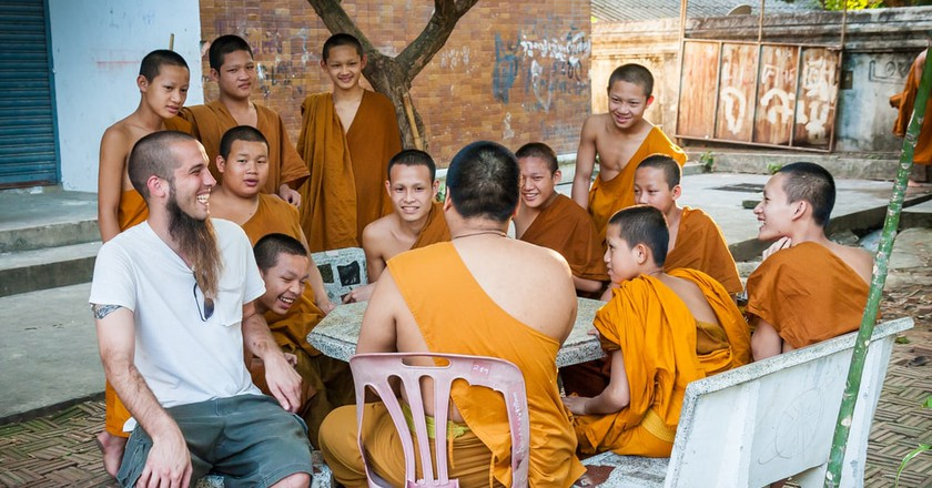 A traveller laughs with monks in Wat Chedi Luang, Thailand | © Faer Out / Shutterstock
