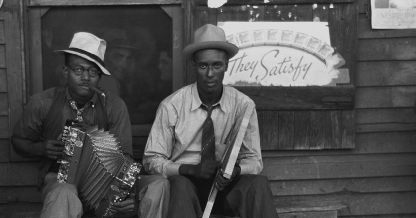 Early Creole musicians playing an accordion and a washboard in front of a store, near Opelousas, Louisiana, courtesy of United States Library of Congress's Prints and Photographs division/WikiCommons