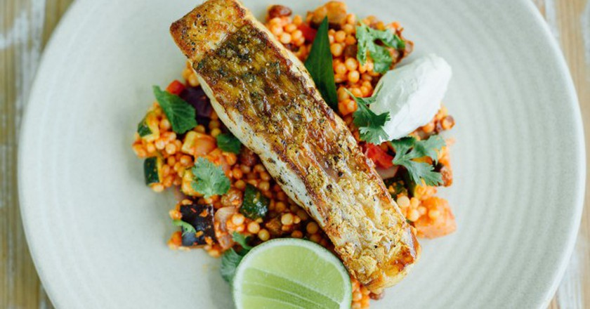 Grilled saltwater barramundi, spiced mediterranean vegetable pearl cous cous, house smoked yoghurt | Courtesy of Noosa Boathouse